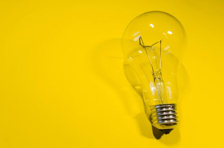 glass light bulb isolted on yellow background. new idea concept