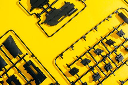 assemble toy handgun with bulllets from the parts concept on yellow background. Plastic model part kits from top view. Foto de archivo