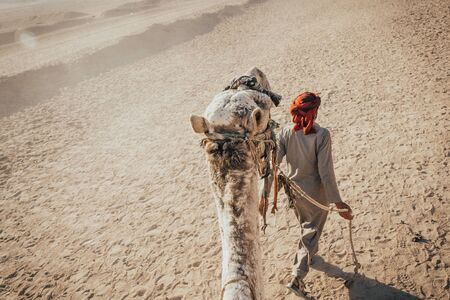 Rear view of a men wearing traditional middle eastern clothes leading a camel in desert. tourist taking a ride on the camel. Stock Photo