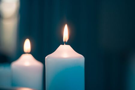 close up view of two white burning candles 스톡 콘텐츠