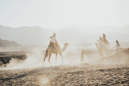 men in middle eastern clothes riding camels in desert