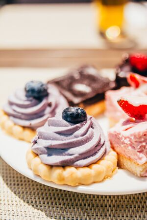 cookies with cream and berries on top. candy bar on white plate Reklamní fotografie