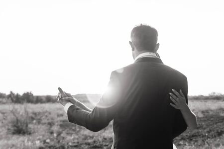 black and white photo of a love couple dancing during sunset Archivio Fotografico
