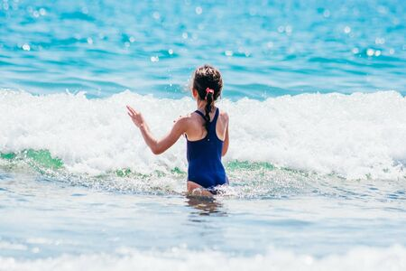 girl in blue swimsuit walks into teal sea from the back view