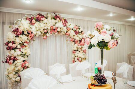 Hochzeit im Restaurant. Braut- und Bräutigamtisch mit Blumenbogen im Hintergrund