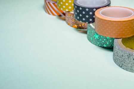 a line of colorful washi tapes isolated on green background from side view