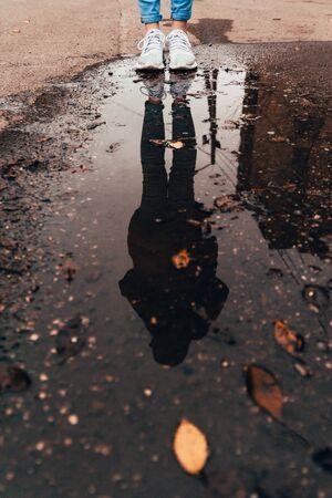reflet d'une femme debout près de la flaque d'eau. saison d'automne à l'extérieur avec des feuilles tombées