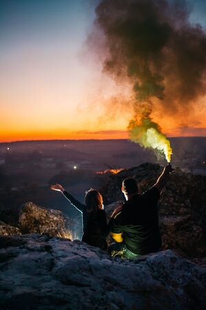 couple and green smoke grenade on the top hill with background of the city lights. Imagens