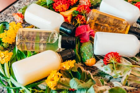 shower gel, shampoo and body lotion in small tubes. travel bottle set mock up with tropic flowers and palm leaves