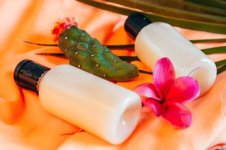 close up view of shampoo in small travel tube in hotel bathroom on orange towel with exotic flowers