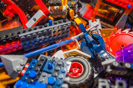 colored toy bricks for kids on the floor background. Playing in plastic lego concept. Pieces and elements of constructor toys. Imagens