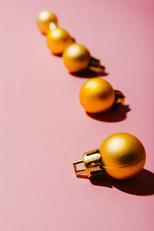 golden christmas tree balls in a line  isolated on pink background