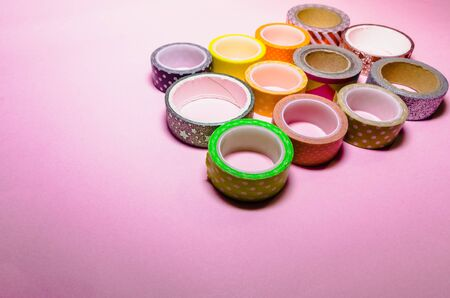 colorful washi tapes isolated on pink background from top view