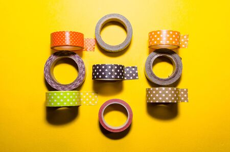 colorful washi tapes isolated on yellow background from top view Imagens