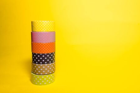 background of colorful washi tapes isolated on yellow background Imagens