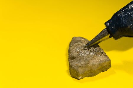 hot glue gun and stone on yellow background