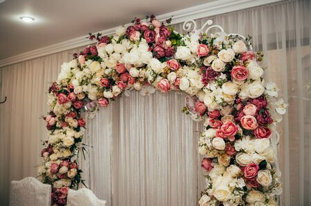 arch with flowers on wedding day in the restaurant