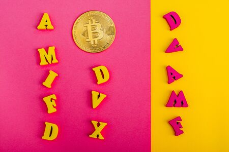 bitcoin on pink and yellow bckground with small colorful  wooden letters
