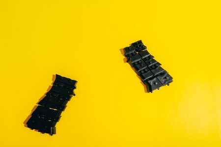 assemble toy handgun with bulllets from the parts concept on yellow background. Plastic model part kits  from top view.