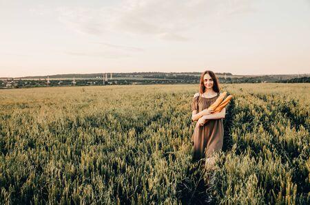 woman in dress making a wreath for head in wheat field Imagens