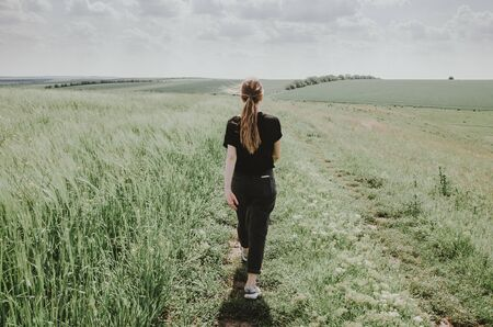 girl walking on the path in the green meadow