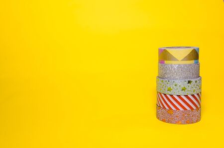 line of colorful washi tapes isolated on yellow background. school stationery