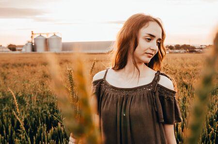 happy woman walking in wheat field during sunrise