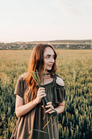 woman in green dress spinning in  wheat field. countryside lifestyle