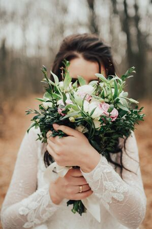 bride covering face with a green bouquet Imagens
