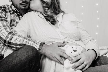 blak and white photo of husband and pregnant wife with a teddy