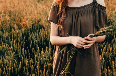 woman in dress stands in green wheat meadow
