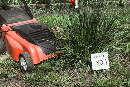 close up view of electric lawn mower cutting a bush with a sign please no Stock fotó - 138276454