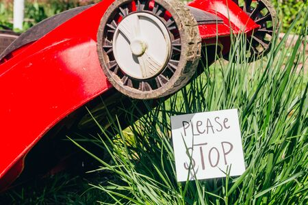 electric lawn mower cutting a bush with a sign please stop. stop destroying the nature. save our planet concept Stock fotó - 138272442