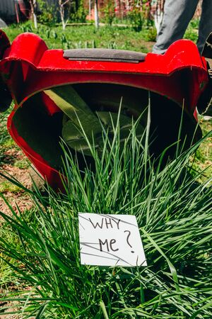 top view of electric lawn mower cutting a bush with a sign why me