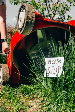 electric lawn mower cutting a bush with a sign please stop. stop destroying the nature. save our planet concept