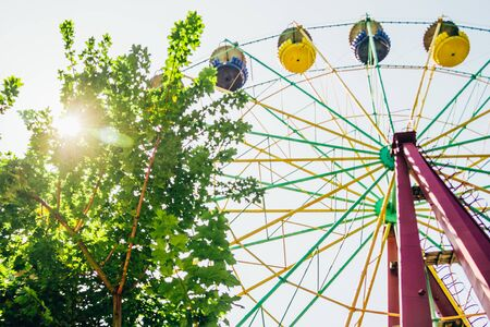 Ferris wheel in the theme park with sun and green leaves Reklamní fotografie