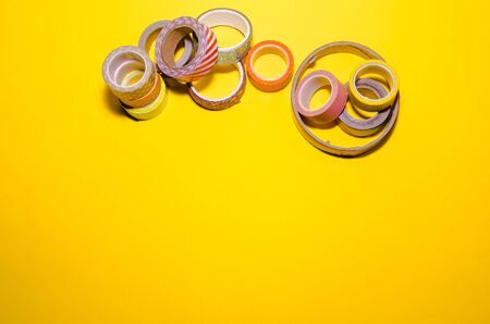 a mess of colorful washi tapes isolated on yellow background. school stationery