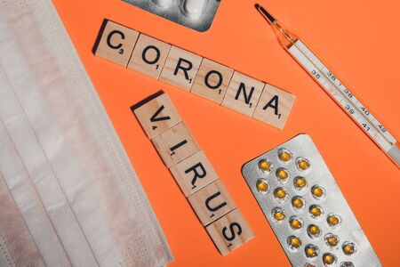 Novel coronavirus disease written with wooden letters. breathing mask, thermometer and pills on orange background. symptoms of the virus