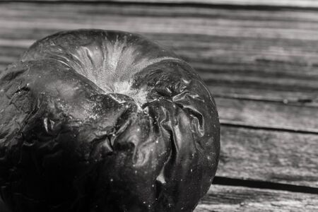 black and white photo of rotting apple close up view. chemicals harm fruits and vegetables concept