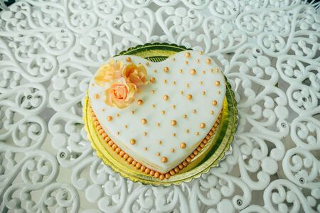wedding white cake in the shape of a heart decorated with flowers Imagens