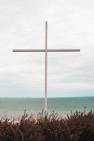 big cross with sea on the background. religion concept Banco de Imagens