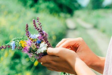 hands holding a bouquet of flowers with green field on background. traveler concept 스톡 콘텐츠 - 146820787