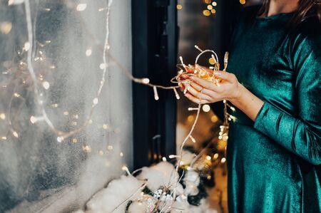 girl holds christmas lights in her hands on bokeh background Reklamní fotografie