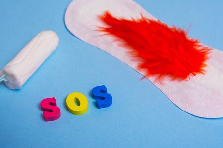 Used feminine sanitary pads and tampon on pink background and word SOS . menstruation time concept .