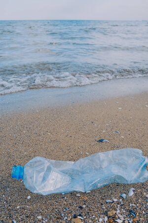 Rubbish plastic disposable bottle on sandy beach around the sea. plastic waste pollution Stok Fotoğraf