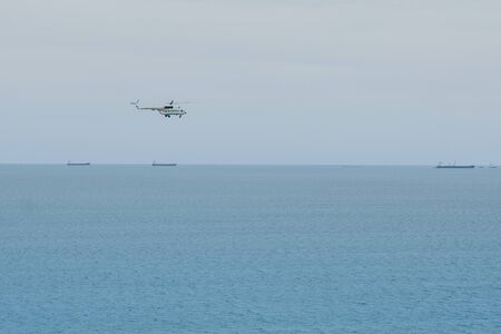 helicopter flies above the sea with big ships on the background