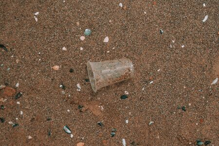 Rubbish plastic disposable cup on sandy beach around the sea. plastic waste pollution