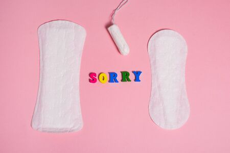 Feminine sanitary pads and tampon on pink background and word sorry . menstruation time concept .