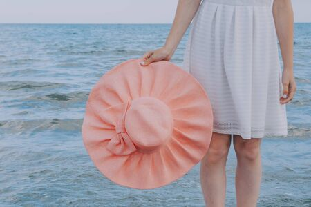 woman in white dress holds pink hat and looks towards the sea. Dreams Come True Concept .