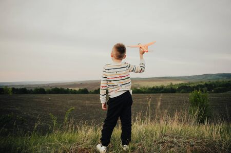 boy playing with orange toy plane outside in the field